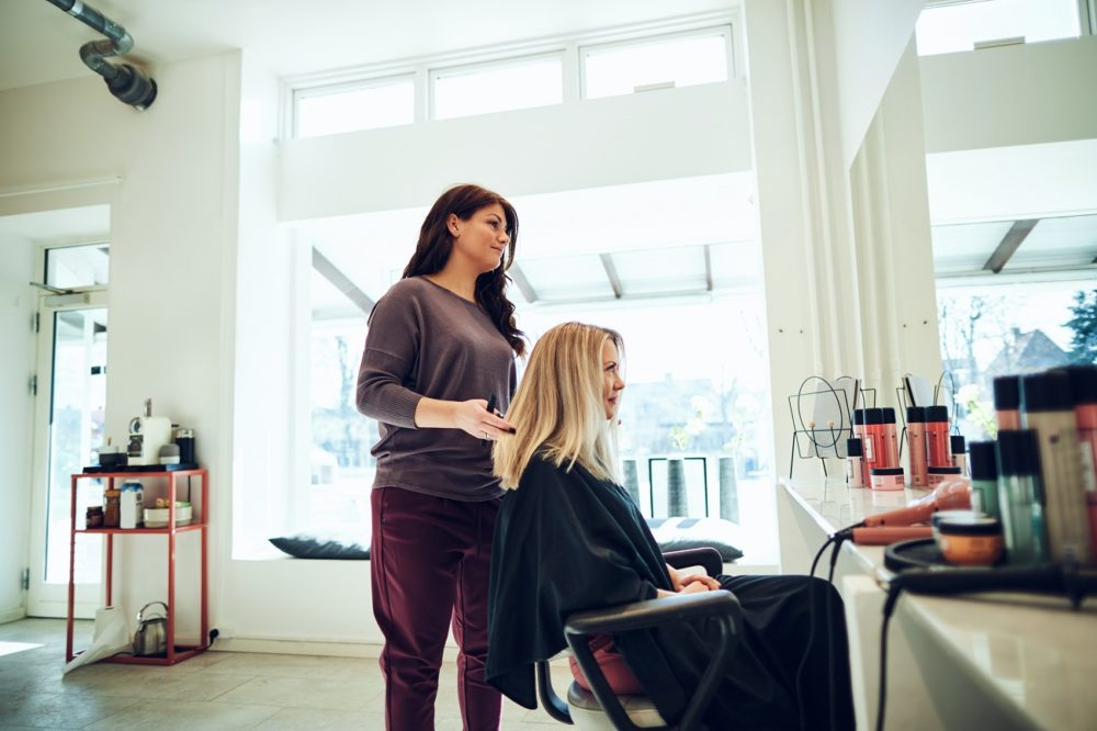 Hairdresser styling a female client's long hair in her salon